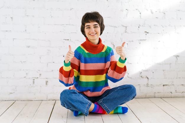 Atractiva mujer joven alegre levantando los pulgares para expresar su aprobación vistiendo suéter corto a rayas ...