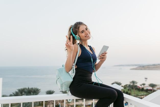 Atractiva mujer joven alegre en ropa deportiva sonriendo, charlando por teléfono, relajándose en el paseo marítimo. amanecer por la mañana, modelo de moda, entrenamiento, música en auriculares, estado de ánimo alegre