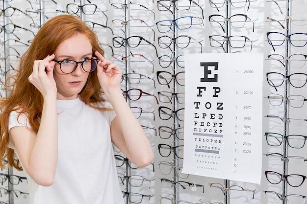 Atractiva mujer joven con anteojos de pie ordenado gráfico de snellen en optica