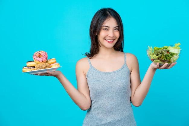 Atractiva mujer joven asiática sosteniendo y eligiendo entre disco de donas o ensalada de verduras en un recipiente de vasos en la pared de color azul aislado