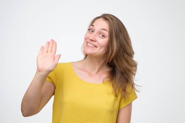 Atractiva mujer joven de aspecto amable sonriendo felizmente, diciendo hola, hola o adiós, agitando la mano