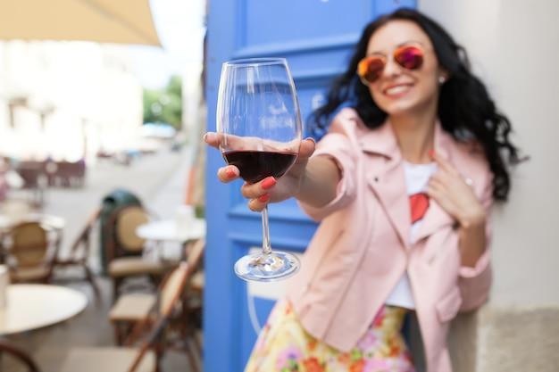 Atractiva mujer joven bebiendo vino en las vacaciones de verano sentado en el café de la calle de la ciudad en traje fresco