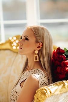 Atractiva mujer joven con cabello rubio en elegante vestido blanco se sienta en un lujoso sofá