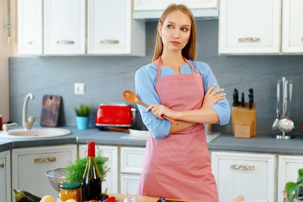 Atractiva mujer joven en delantal rojo de pie en su cocina