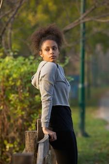 Atractiva mujer joven ejercicio descansando al aire libre