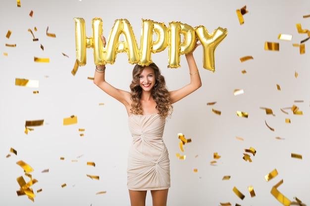 Atractiva mujer joven y elegante celebrando el año nuevo, sosteniendo globos de aire letras felices, confeti dorado volando, sonriendo feliz, aislado, vestido de fiesta