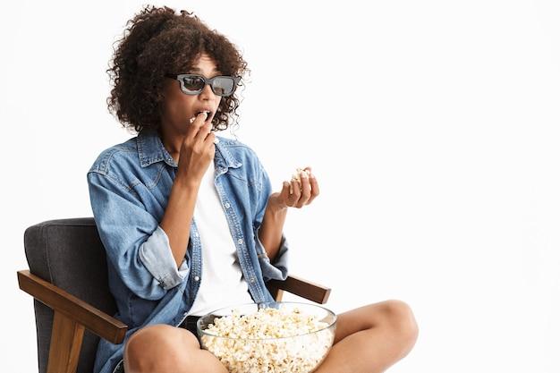 Atractiva mujer joven emocionada vistiendo denim sentado en una silla aislada sobre una pared blanca, viendo una película, comiendo palomitas de maíz