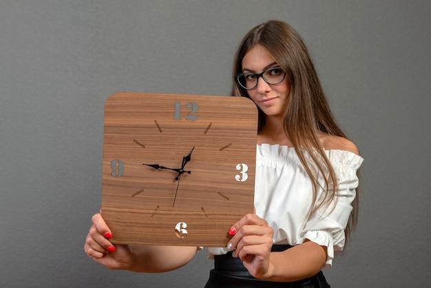 Atractiva mujer joven emocional sobre fondo oscuro muestra un reloj