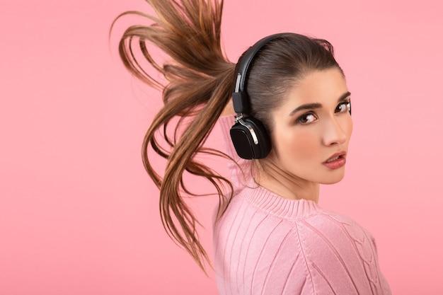Atractiva mujer joven escuchando música en auriculares inalámbricos con suéter rosa sonriendo feliz estado de ánimo positivo posando sobre fondo rosa