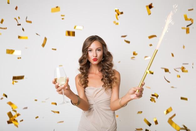 Atractiva mujer joven con estilo celebrando el año nuevo, bebiendo champán, confeti dorado volando, sonriendo feliz, aislado, vestido de fiesta