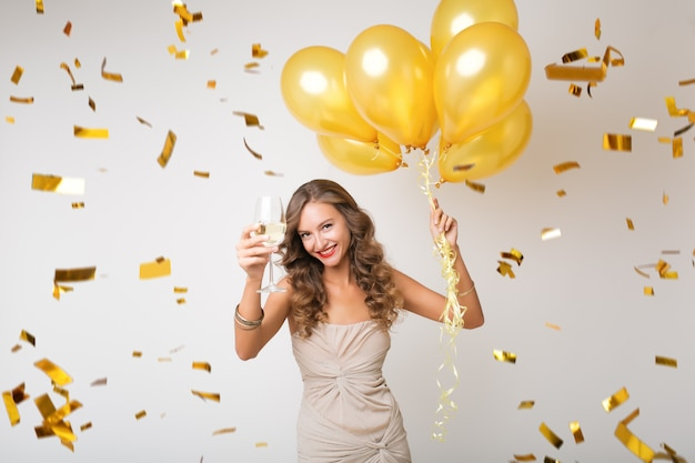 Atractiva mujer joven con estilo celebrando el año nuevo, bebiendo champán sosteniendo globos de aire, confeti dorado volando, sonriendo feliz, aislado, vestido de fiesta