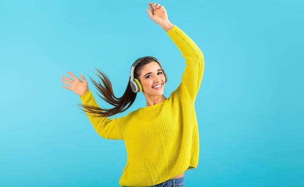 Atractiva mujer joven con estilo escuchando música en auriculares inalámbricos feliz vistiendo suéter de punto amarillo estilo colorido moda posando aislado sobre fondo azul agitando cola de pelo largo