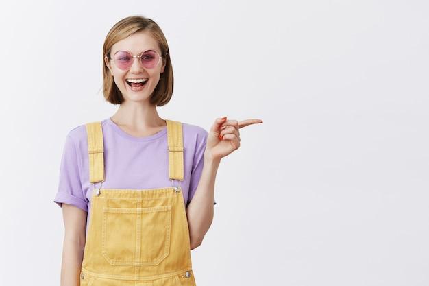 Atractiva mujer joven con estilo en gafas de sol sonriendo, recomendar promoción, señalar con el dedo a la derecha
