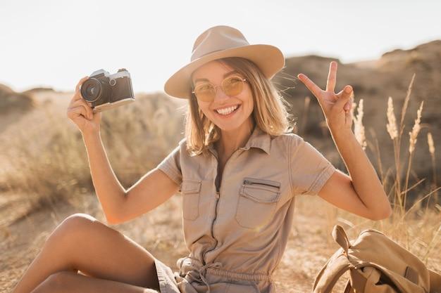 Atractiva mujer joven con estilo en vestido caqui en el desierto, viajando en áfrica en un safari, con sombrero y mochila, tomando fotos con una cámara vintage