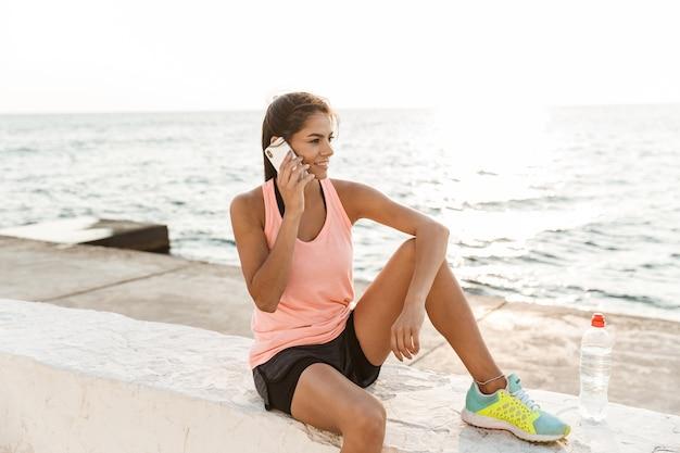 Atractiva mujer joven fitness mediante teléfono móvil mientras descansa en la playa después de trotar, hablando