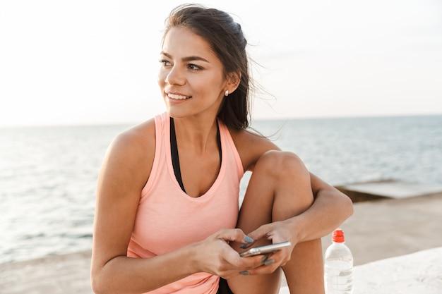 Atractiva mujer joven fitness mediante teléfono móvil mientras descansa en la playa después de trotar