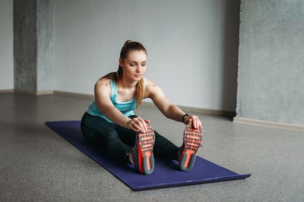 Atractiva mujer joven en forma ropa deportiva fitness chica haciendo estiramientos en la clase de entrenamiento de estudio en casa