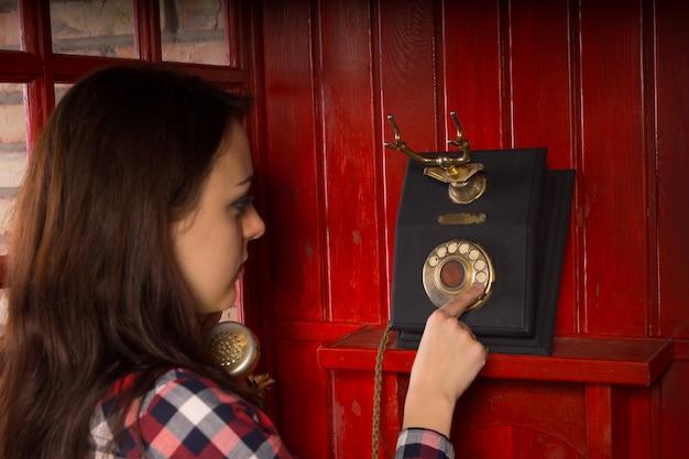 Atractiva mujer joven haciendo una llamada telefónica en un antiguo teléfono de marcación giratoria vintage en una cabina de teléfono de madera roja