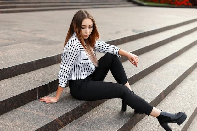 Atractiva mujer joven en jeans de moda en una lujosa blusa de rayas con elegantes zapatos de cuero se sienta en los escalones de la vendimia en la ciudad en un cálido día de primavera al aire libre
