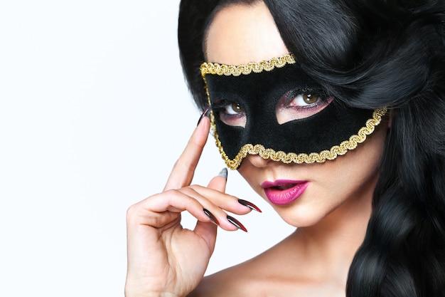 Atractiva mujer joven con máscara de venecia