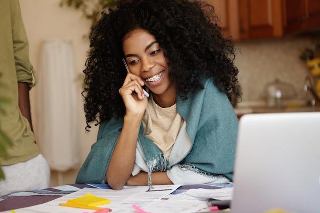 Atractiva mujer joven con peinado afro abd tirantes conversando por teléfono y sonriendo felizmente mientras hace el papeleo en casa, sentada en la mesa de la cocina con muchos papeles y computadora portátil
