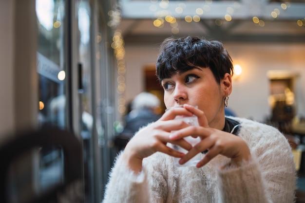 Atractiva mujer joven con pelo corto bebiendo agua en un café y mirando por la ventana