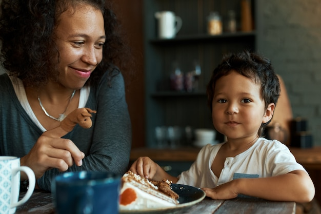 Atractiva mujer joven con pelo rizado sentado en la mesa de la cocina en el desayuno con su hijo