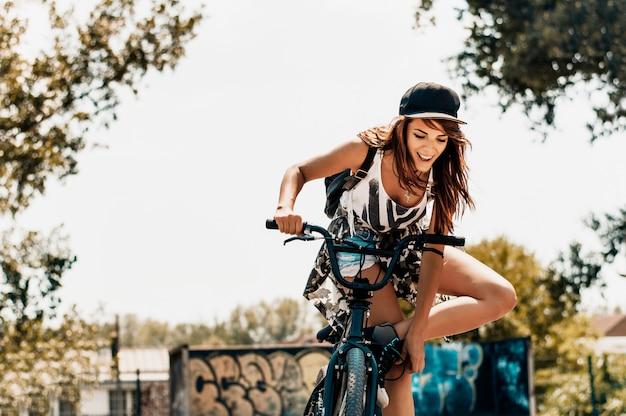 Atractiva mujer joven de pie junto a su bicicleta