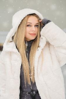 Atractiva mujer joven posando en el parque cubierto de nieve