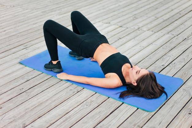 Atractiva mujer joven practicando ejercicios de yoga acostado sobre una alfombra sobre tablas de madera