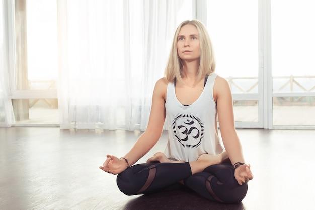 Atractiva mujer joven practicando yoga sentado en posición de loto cerca de una ventana grande en casa