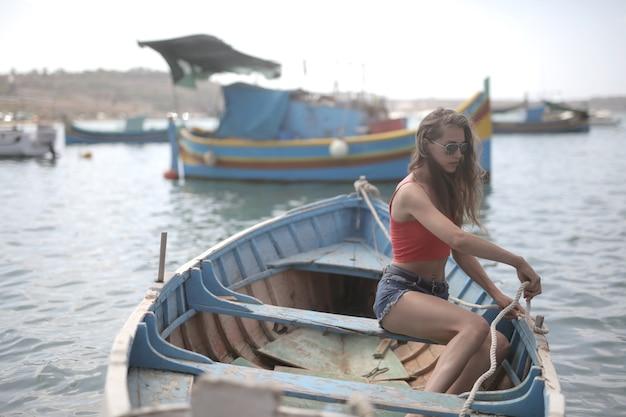 Atractiva mujer joven sentada en un barco de madera en el agua bajo la luz del sol durante el día
