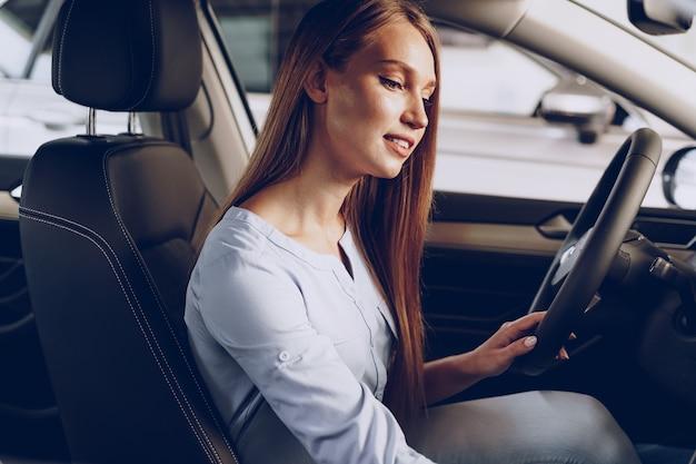 Atractiva mujer joven sentada en un coche nuevo en la sala de exposiciones