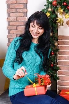 Atractiva mujer joven sentada en un interior de navidad, tiene caja de regalo roja