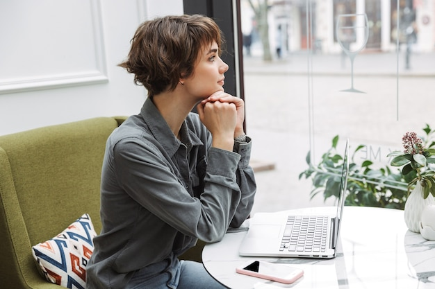 Atractiva mujer joven sentada en la mesa de café en el interior, trabajando en la computadora portátil, analizando documentos