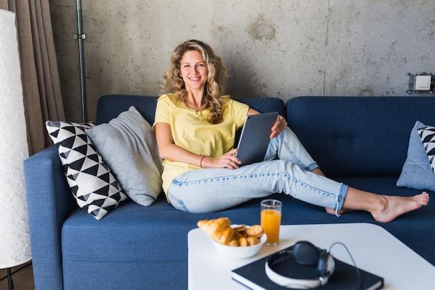 Atractiva mujer joven sentada relajada en el sofá en casa sosteniendo la tableta, viendo en línea