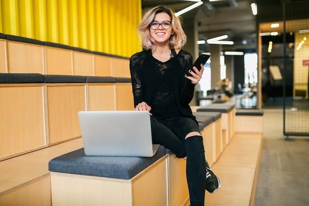 Atractiva mujer joven sentada en la sala de conferencias, trabajando en la computadora portátil, con gafas, auditorio moderno, educación de estudiantes en línea, autónomo, sonriendo, usando el teléfono inteligente, mirando a la cámara