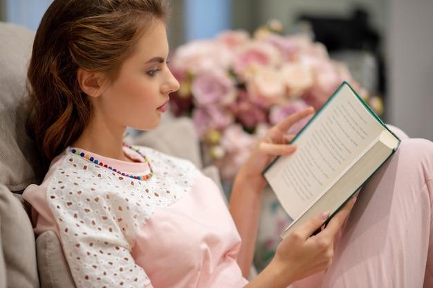 Atractiva mujer joven sentada en el sofá leyendo un libro disfruta de descanso.