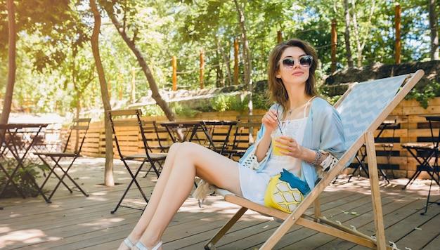 Atractiva mujer joven sentada en la tumbona en traje de moda de verano, estilo hipster, vestido blanco, capa azul, gafas de sol, beber limonada, accesorios elegantes, piernas largas y flacas relajantes en sandalias