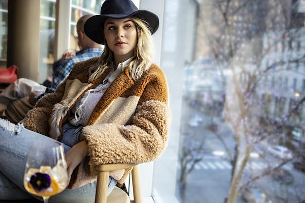 Atractiva mujer joven con un sombrero negro sentado en un café junto a una pared de cristal