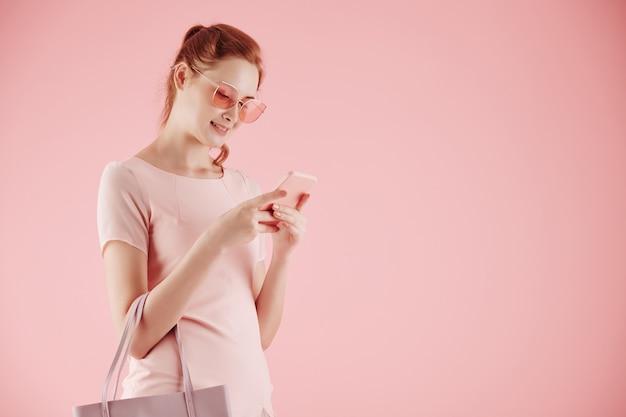 Atractiva mujer joven sonriente en gafas de sol enviando mensajes de texto a amigos, aislado en rosa claro