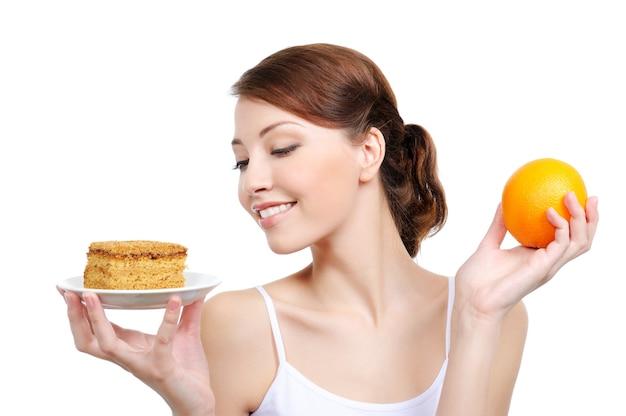 Atractiva mujer joven sosteniendo apetitoso pastel y naranja saludable