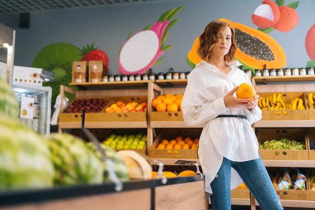 Atractiva mujer joven sosteniendo en las manos grandes granadas frescas posando de pie en la tienda de frutas