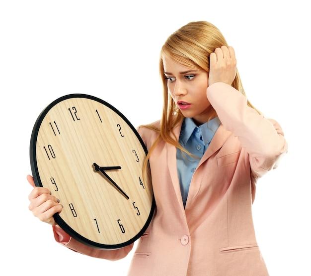 Atractiva mujer joven sostiene un reloj, aislado en blanco