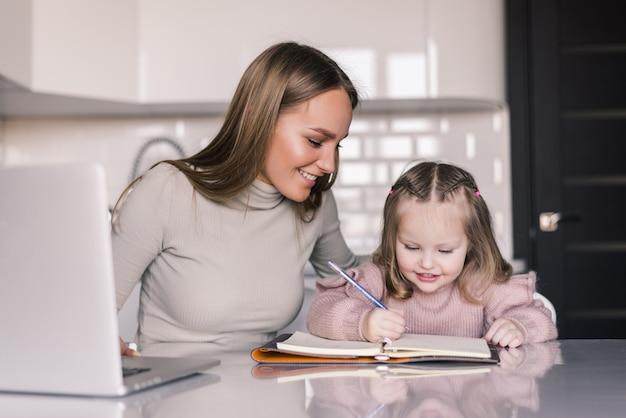 Atractiva mujer joven y su pequeña hija linda están sentadas a la mesa y haciendo la tarea juntas