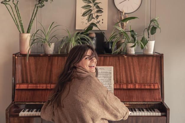 Atractiva mujer joven tocando el piano en casa
