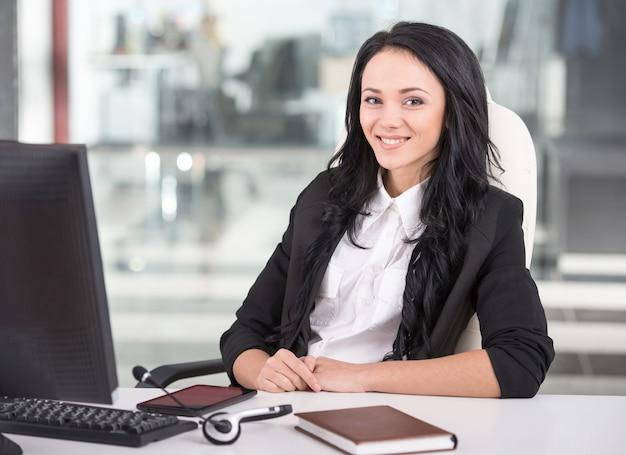 Atractiva mujer joven está trabajando en un centro de llamadas.