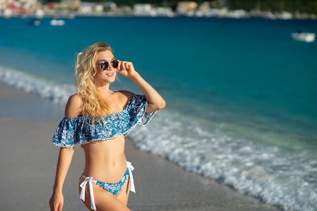 Atractiva mujer joven con traje de baño en la playa de arena tropical en verano para vacaciones viajes vacaciones