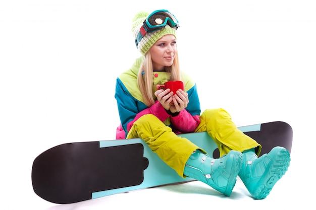 Atractiva mujer joven en traje de esquí y gafas de esquí se sientan en snowboard, sostienen la taza roja