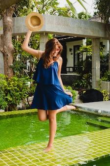 Atractiva mujer joven en vestido azul y sombrero de paja con gafas de sol rosas y bailando en la piscina